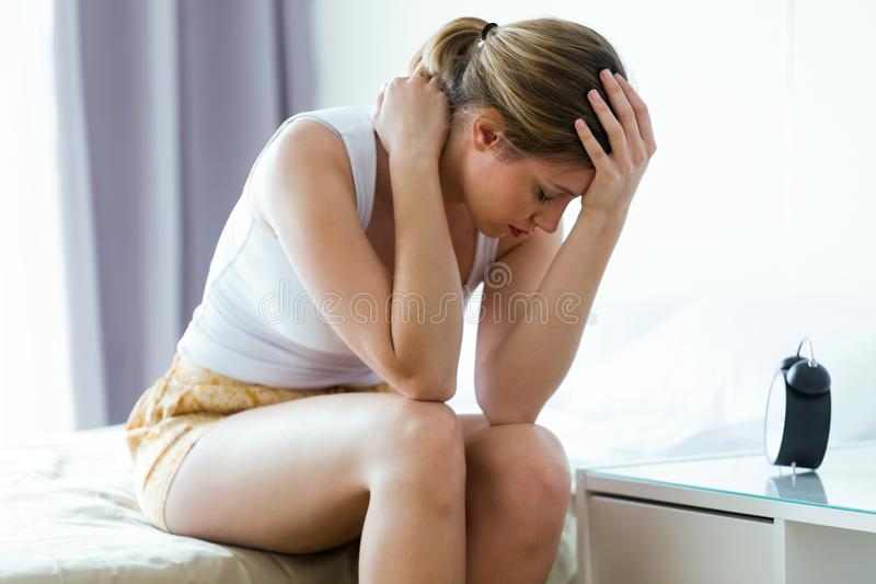 Unhappy lonely depressed young woman sitting on bed at home. Depression concept. royalty free stock images