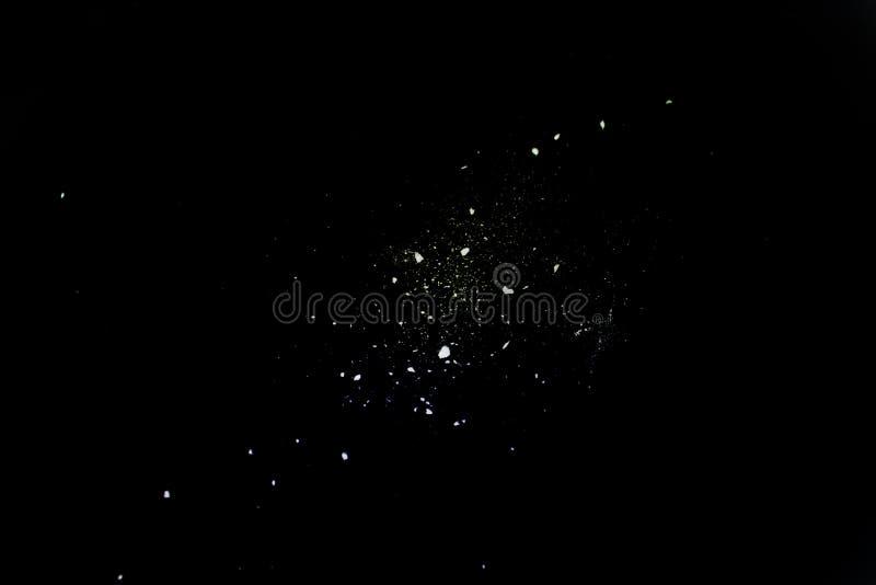 shot of white powder on black background stock images