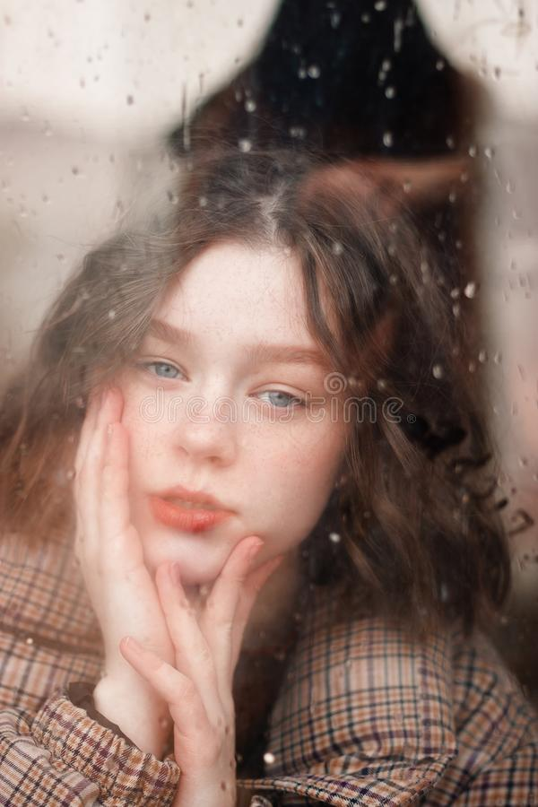 Shot through the window with raindrops. Beautiful curly girl stock photos