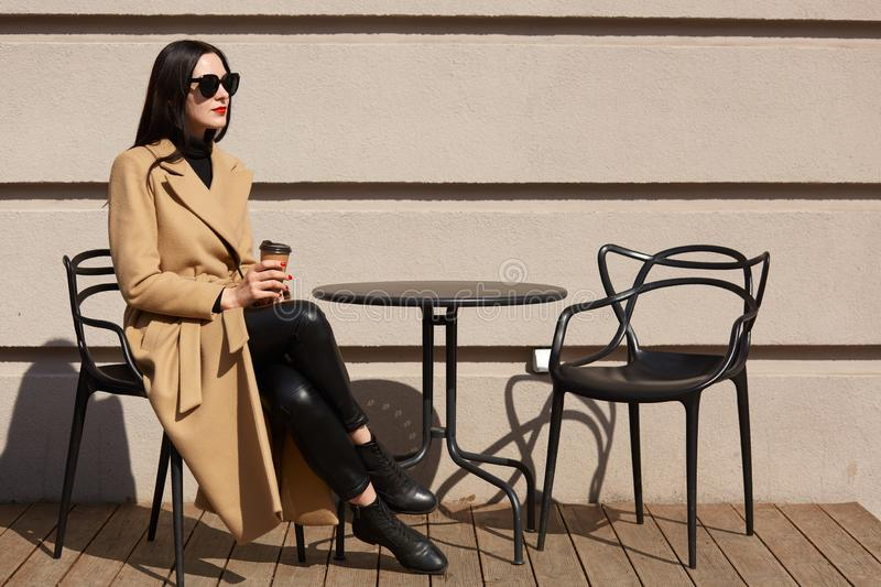 Shot of woman wearing fashionable coat having breakfast in cozy street outdoor cafe and drinking coffee from paper mug. Girl sits royalty free stock images