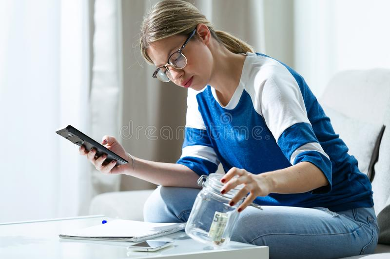 Worried young woman using calculator and looking her savings while sitting on sofa at home. Shot of worried young woman using calculator and looking her savings stock photo