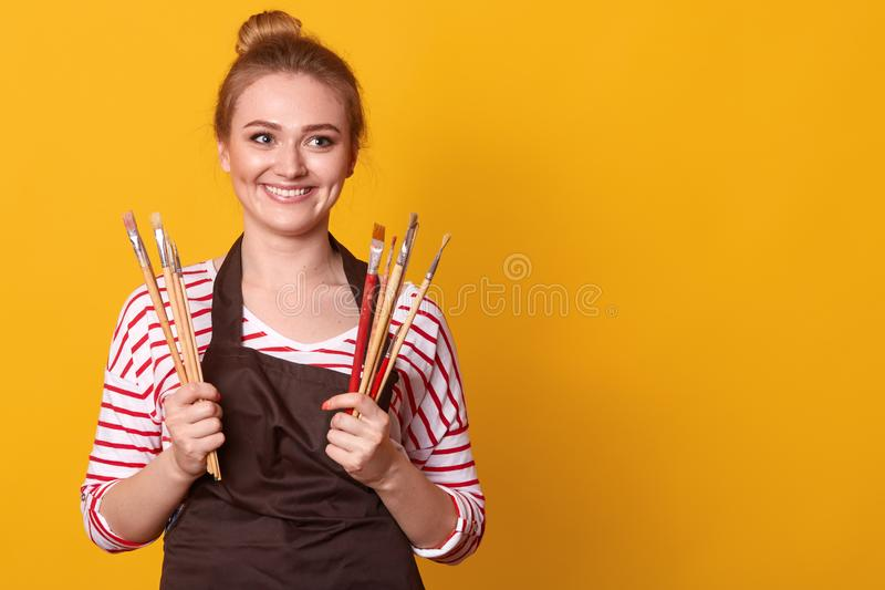 Shot of young caucasian painter working in her studio. Creative young woman painting on canvas in her workshop.  royalty free stock photos