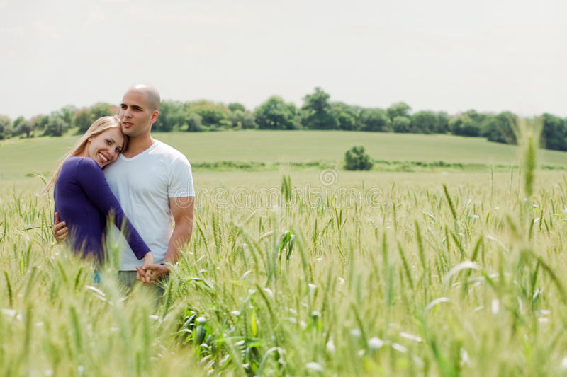 Shot of young couple hugging and holding hands stock image