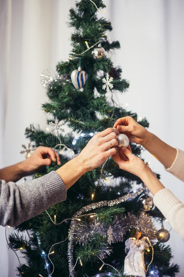 Cute, young couple decorating a Christmas tree stock photography