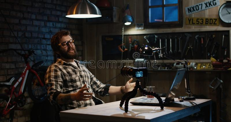 Young man talking on camera in a workshop royalty free stock image