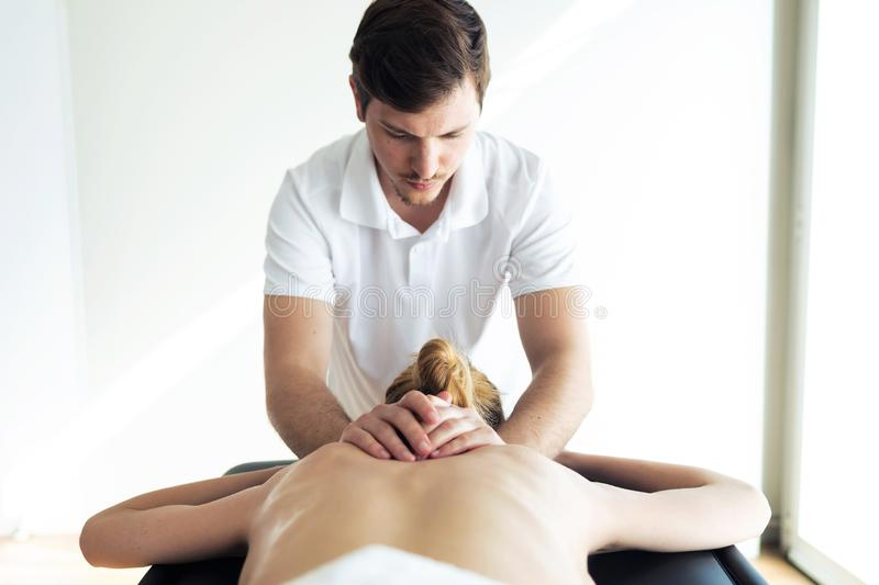 Young physiotherapist doing a back treatment to the patient in a physiotherapy room stock images