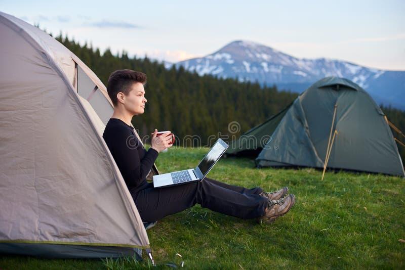 Young woman using laptop outdoors stock photos