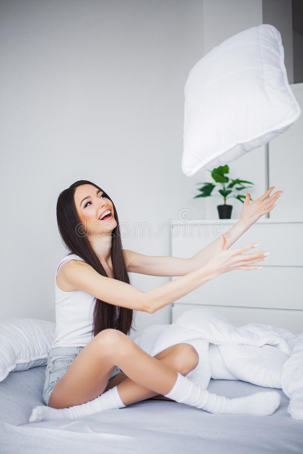 Shot of a young woman sitting on a bed royalty free stock photos