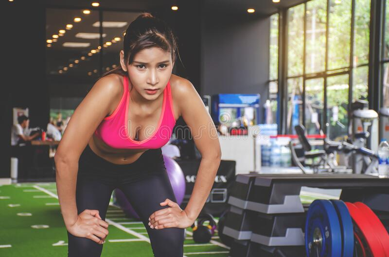 Shot of young woman in sportswear bending with her hands on knees at the gym. Fitness woman looking tired after exercising at gym stock images