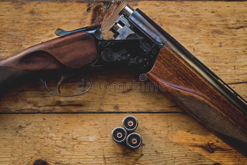 Shotgun charged with bullets and spare bullets on wooden floor, royalty free stock photos
