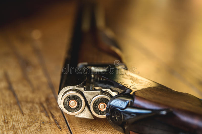Shotgun charged with bullets and spare bullets on wooden floor, royalty free stock photography