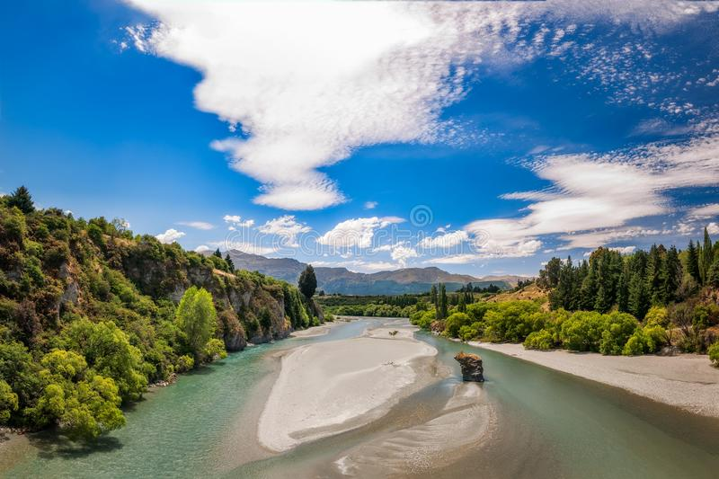 Shotover River View in Queenstown, NZ. View from the old Bridge towards Coronet and Brow Peaks, over Shotover River, formerly one of the richest gold bearing stock photos