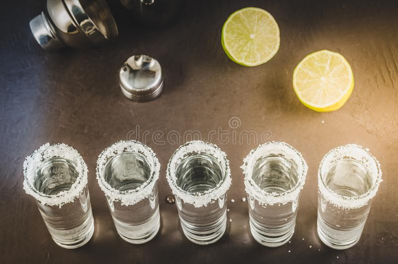 shots of tequila and pieces of lime ona dark background/shots of tequila and pieces of lime ona dark background. Top view royalty free stock photography