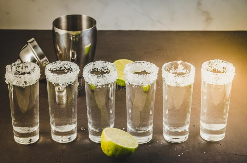 shots of tequila and pieces of lime and shaker/shots of tequila and pieces of lime and shaker on a black stone table royalty free stock image