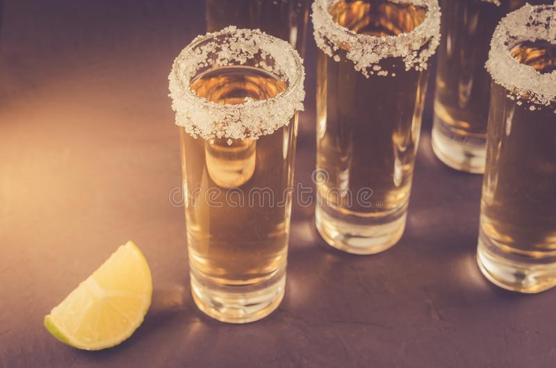 Shots of tequila and pieces of lime/shots of tequila and pieces of lime. Toned and copyspace. Bar vodka salt background table cocktail lemon liquor mexican stock image