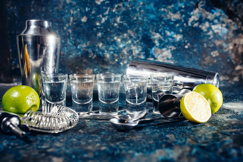 Shots of tequila or strong drink in small glasses, with lime garnish ready to be served royalty free stock photography