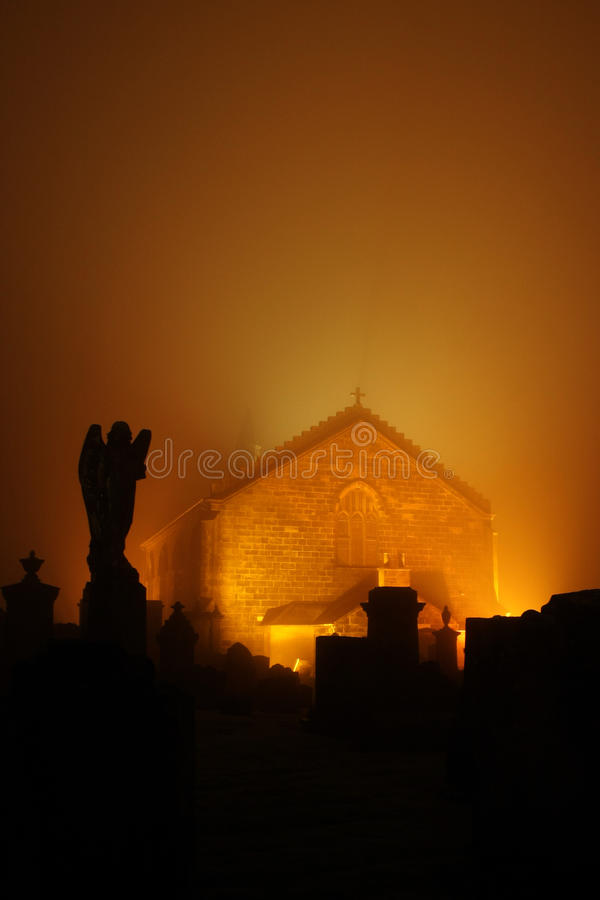 Shotts Kirk and cemetery. Shotts kirk or church illuminated orange at night with silhouetted cemetery in foreground, North Lanarkshire, Scotland stock photography