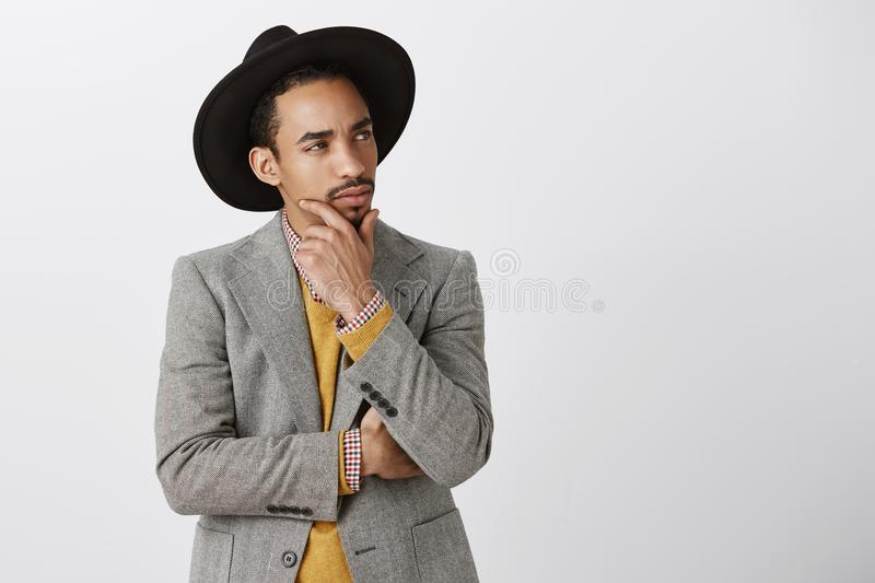 Should I make investition or not. Portrait of thoughtful focused attractive dark-skinned male in stylish clothes looking royalty free stock photos