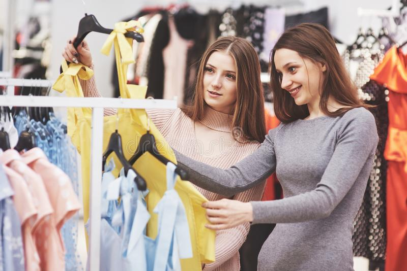 We should look at new dresses Rear view of two beautiful women with shopping bags looking away with smile while walking royalty free stock image