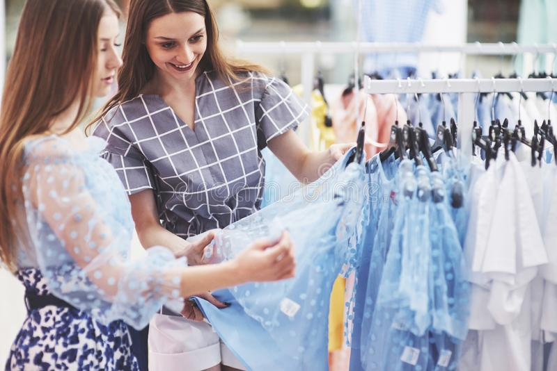 We should look at new dresses Rear view of two beautiful women with shopping bags looking away with smile while walking stock image