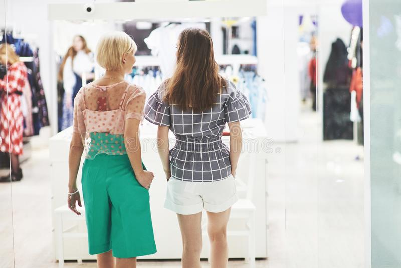 We should look at new dresses Rear view of two beautiful women with shopping bags looking away with smile while walking stock photos