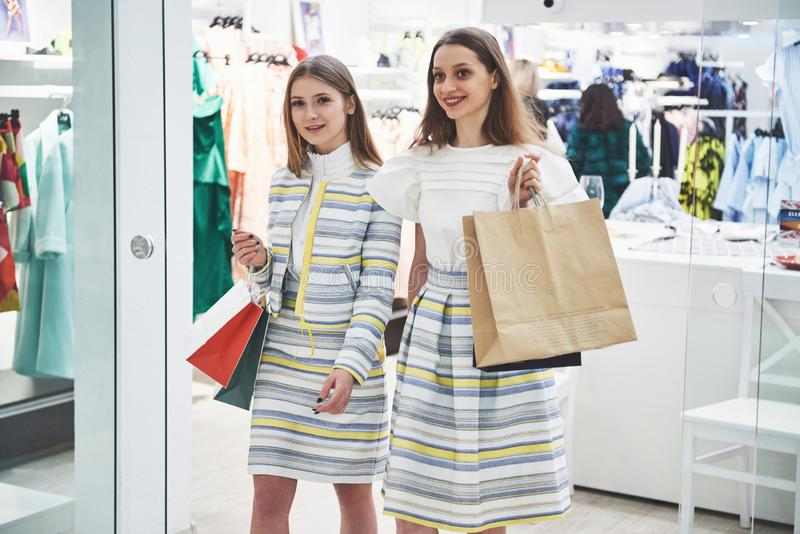 We should look at new dresses Rear view of two beautiful women with shopping bags looking away with smile while walking royalty free stock photography