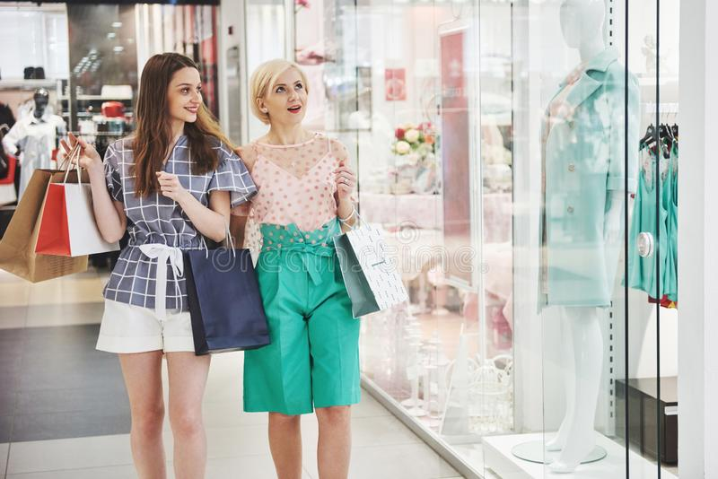 We should look at new dresses Rear view of two beautiful women with shopping bags looking away with smile while walking royalty free stock photo