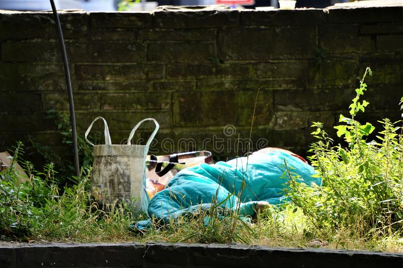 Homeless person in turquoise sleeping bag. Shoulder bags, canvas, and plastic hold belongings of man or woman lying down in weeds next to stone wall.  City royalty free stock image