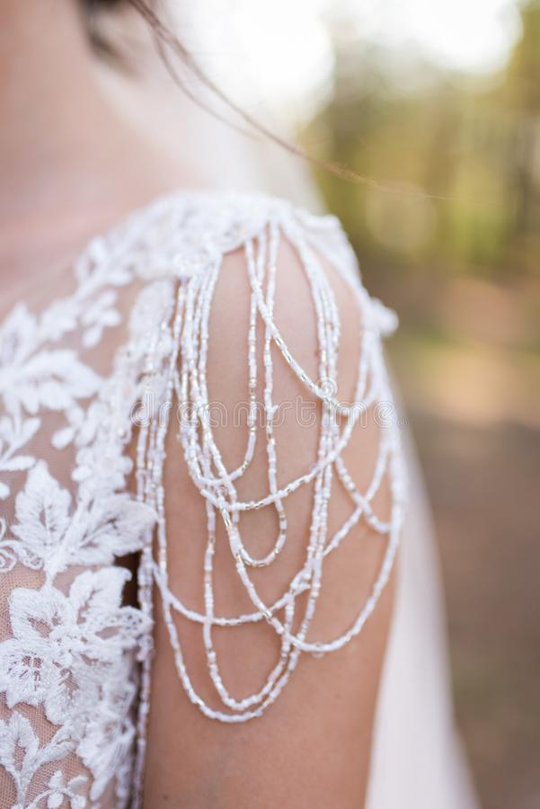 On the shoulder of the bride wakes a piece of a wedding dress with a lot of beads. . On the shoulder of the bride wakes a piece of a wedding dress with a lot of royalty free stock images