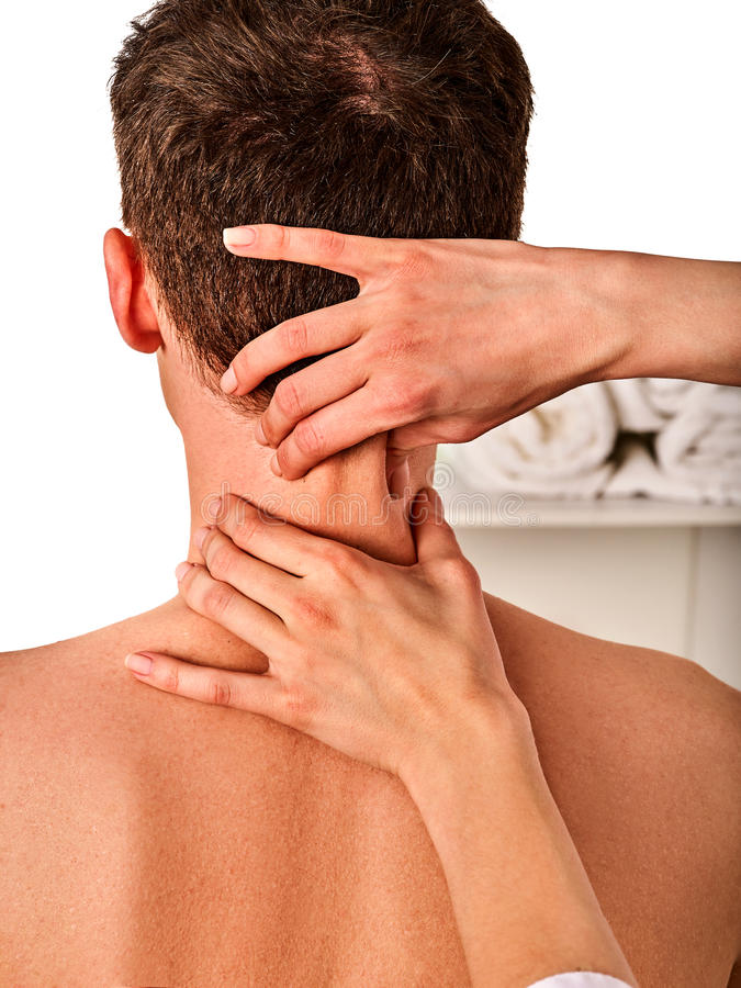 Shoulder and neck massage for man in spa salon. Doctor making neck therapy in rehabilitation center . Folded towels in the background stock photography