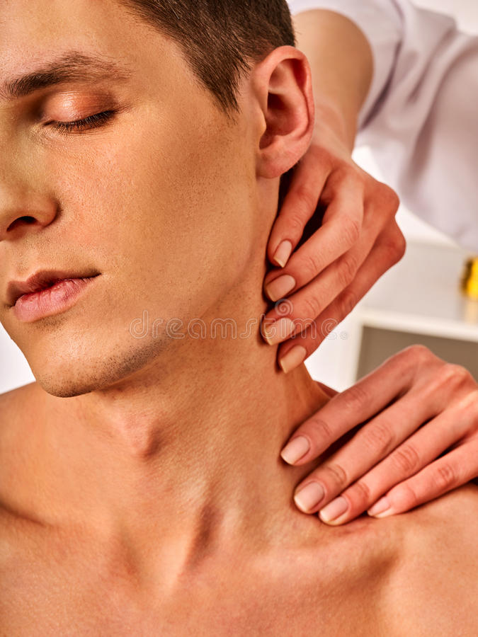 Shoulder and neck massage for man in spa salon. Doctor making therapy in rehabilitation center . Folded towels in the background. Correction of dislocation of stock photography
