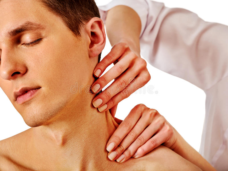 Shoulder and neck massage for man in spa salon. Doctor making therapy in rehabilitation center. Folded towels in the background. Massage the neck in an elite royalty free stock photo