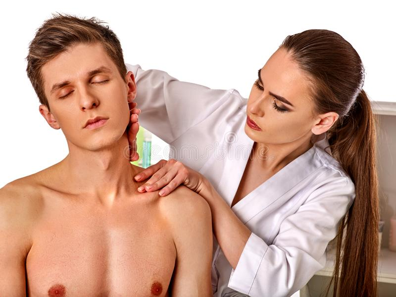 Shoulder and neck massage for man in spa salon. Shoulder and neck massage for men in spa salon. Doctor making neck therapy in rehabilitation center on isolated royalty free stock photo