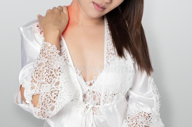 Shoulder pain or Dislocated shoulder. In a woman, Ache pinched nerve in the neck or shoulder, Women wear white nightgown & long sleeve satin robe with floral stock photography