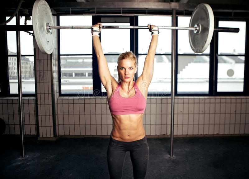 Shoulder Press Fitness Exercise. Fit woman performing a shoulder press exercise stock photography