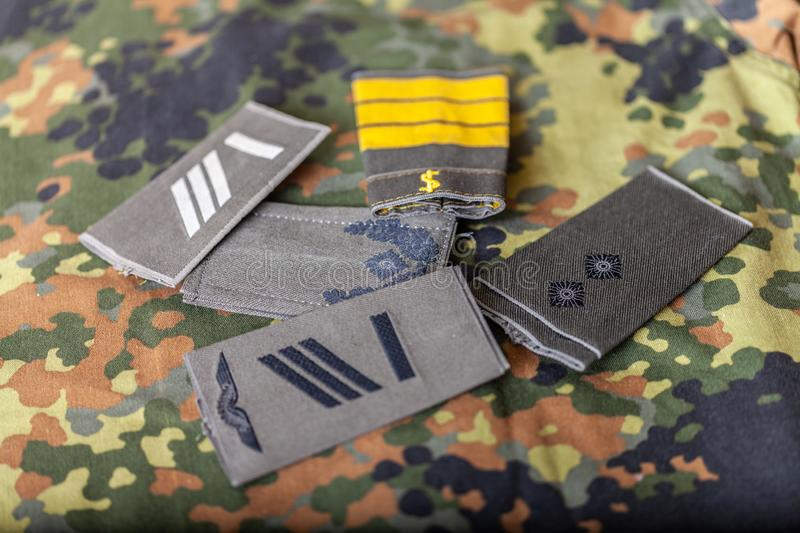 German shoulder ranks on a camouflage background. Shoulder ranks on a camouflage background royalty free stock photo
