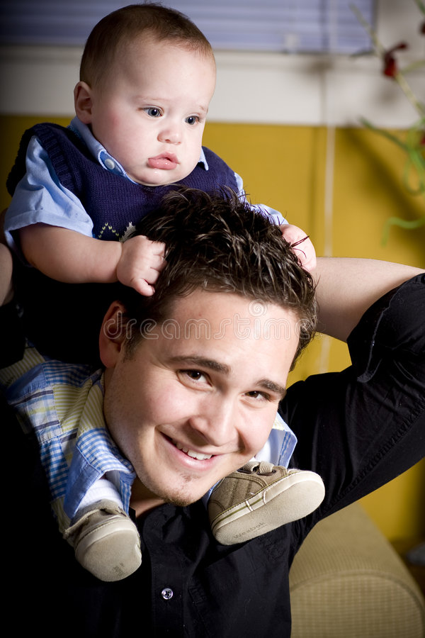 On The Shoulders. Baby boy rests on daddy's shoulder royalty free stock images
