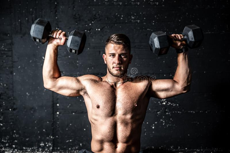 Young strong sweaty man shoulders workout training with two dumbbells in the gym dark image with shadows. Shoulders training, Young strong sweaty man shoulders royalty free stock image