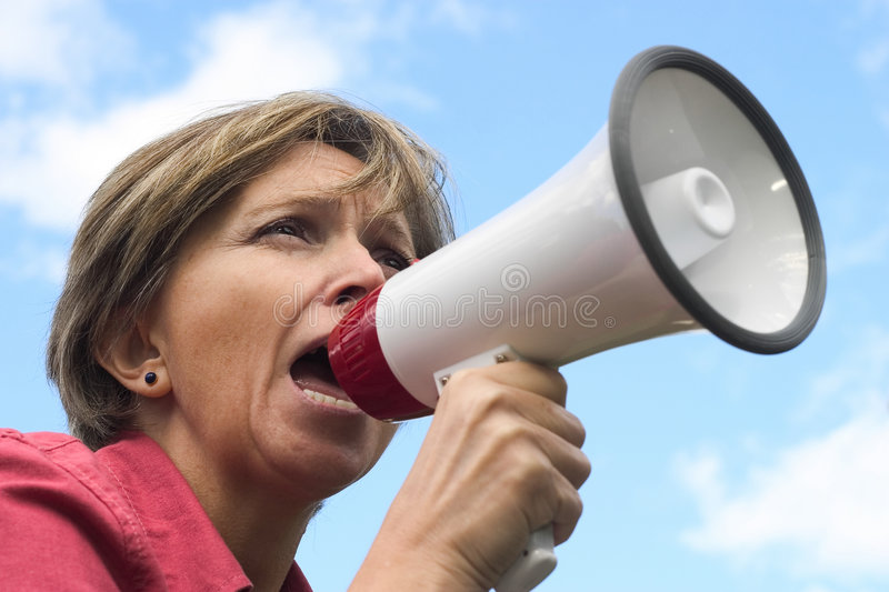Shouting. Middle-aged woman shouting through the megaphone royalty free stock photos
