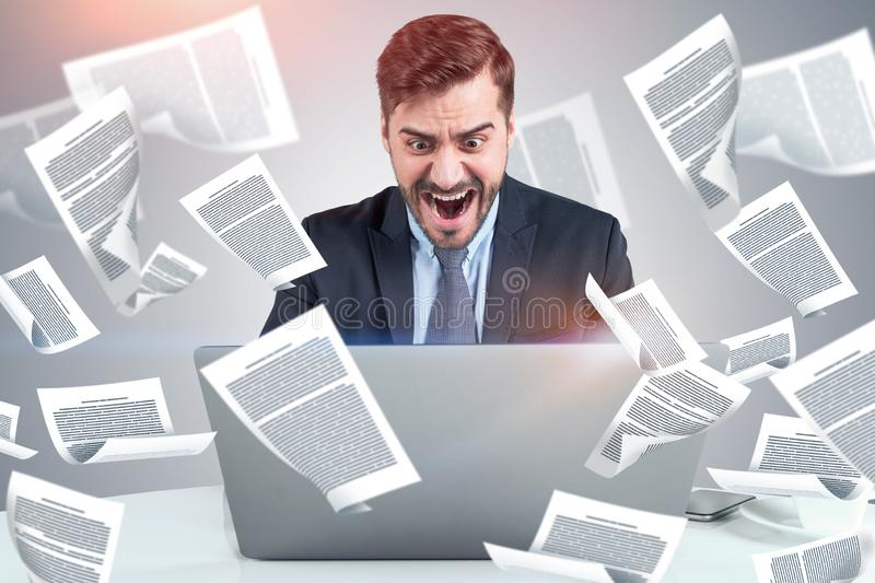 Shouting businessman with laptop, documents stock images