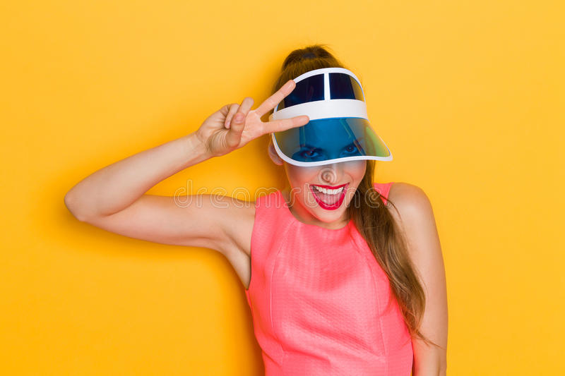 Shouting Girl In Blue Sun Visor Cap. Young woman in pink dress and sun visor posing against yellow background and showing peace sign royalty free stock photos