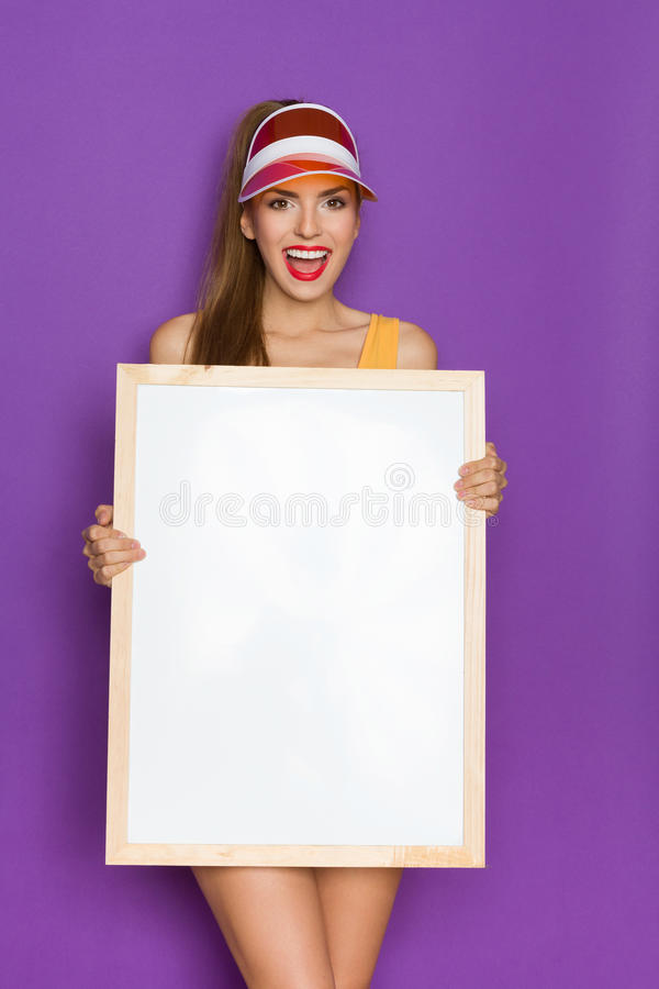 Shouting Girl Holding White Picture. Shouting young woman in orange sun visor holding white blank picture in wooden frame.Three quarter length studio shot on royalty free stock image