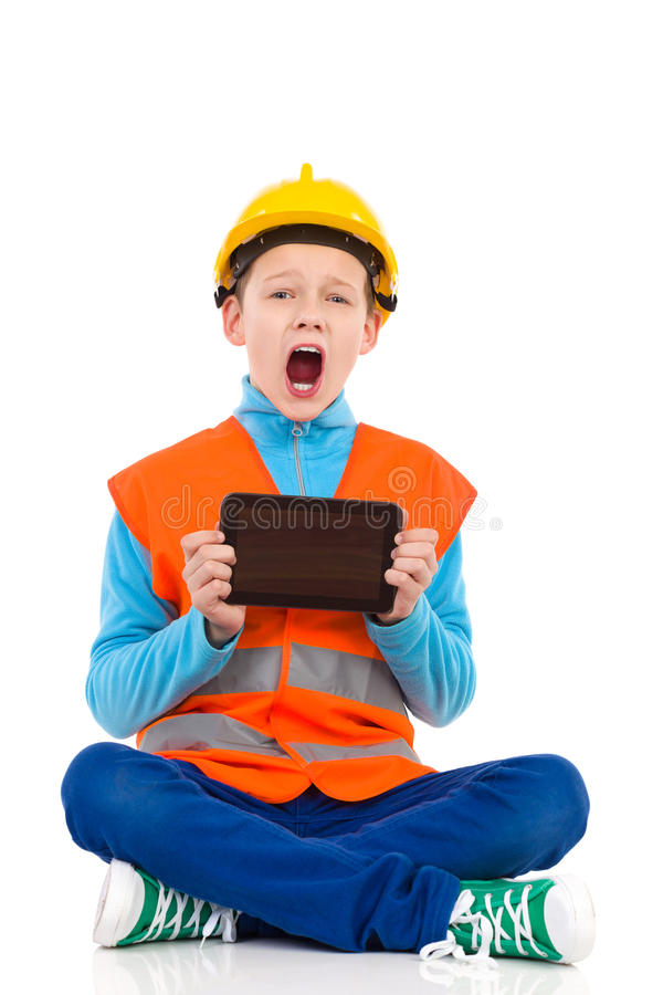 Shouting little construction worker showing a digital tablet. Young boy in yellow hard hat and orange reflective vest holding a digital tablet and shouting. Full stock photo