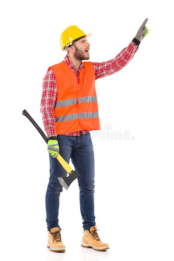Shouting Lumberjack Is Pointing And Directing. Shouting Man In Reflective Vest And Yellow Helmet Is Holding Axe, Looking Away And Pointing. Full Length Studio stock photos