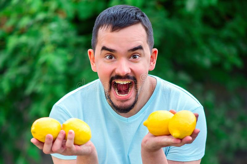 Shouting man holding in hands four yellow lemons. Man with wide open mouth standing outdoor with citrus fruits stock image