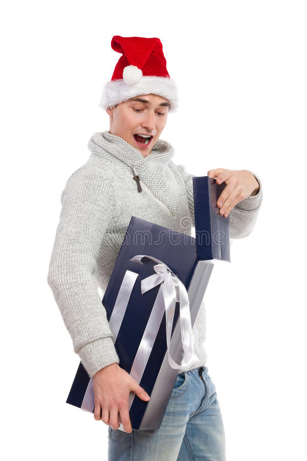 Shouting man opening a gift. Young man in santa's hat opening a gift. Three quarter length studio shot isolated on white royalty free stock photos