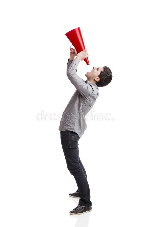 Shouting into a megaphone. Young man shouting into a megaphone over a white background royalty free stock photos