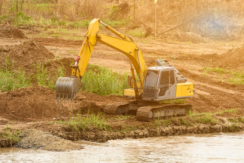 Shovel bucket on river bank , lift loads, construction machinery royalty free stock images