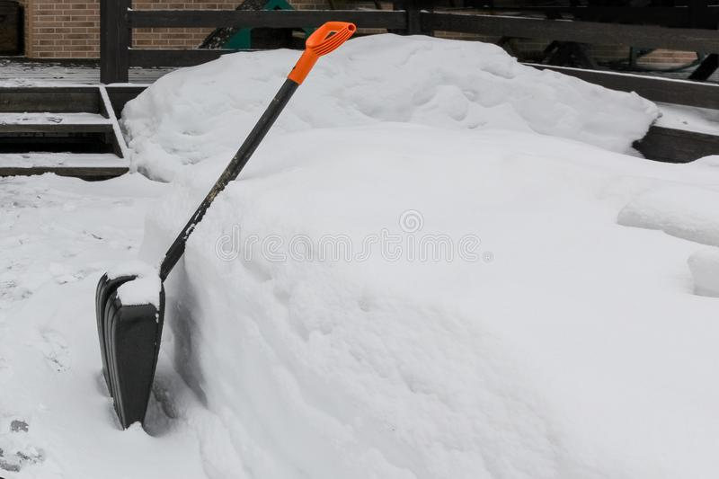 Shovel for cleaning remove tracks from snow in country house in winter stock photography