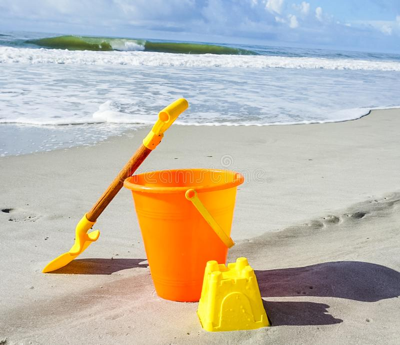 A Shovel and Pail on the Beach. Ready to build a sandcastle with this shovel and pail on the beach stock photos